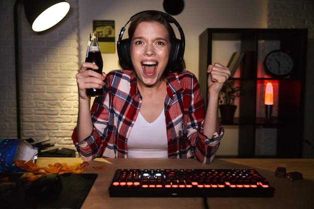 Donna emozionante che indossa la cuffia avricolare che gioca giochi in linea sul computer, mangiando spuntini
