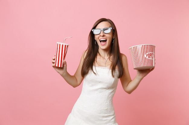 Donna eccitata in abito bianco, occhiali 3d che guardano film, tenendo in mano un secchio di popcorn tazza di plastica di soda o cola