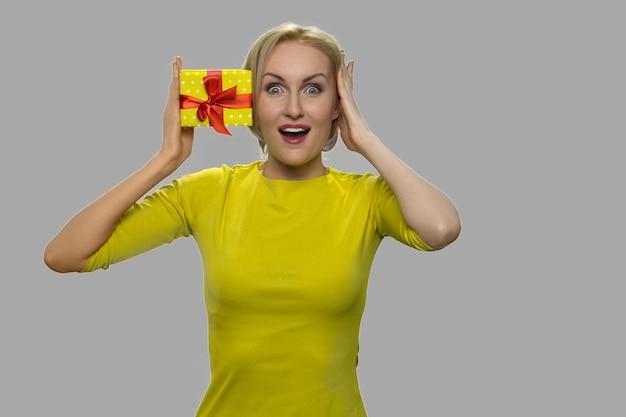 Donna emozionante con confezione regalo su sfondo grigio. felice donna scioccata con la presente casella guardando la fotocamera. concetto di sorpresa.