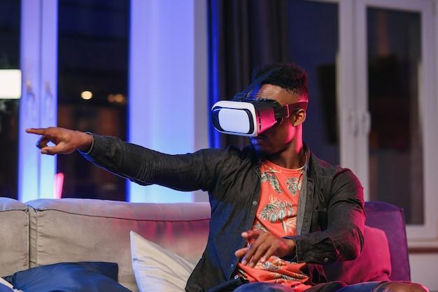 Giovane uomo afroamericano emozionante che estende la mano in avanti, facendo uso della cuffia avricolare di realtà virtuale che si siede sul letto, spazio della copia