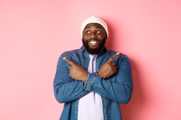 Eccitato giovane afro-americano che punta di lato, mostrando due scelte e prendendo una decisione, sorridendo felice, in piedi su sfondo rosa