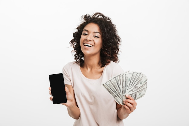 Giovane donna americana emozionante con l'acconciatura afro e il grande fan della tenuta di sorriso delle banconote in dollari e del telefono cellulare d'argento, isolato sopra la parete bianca