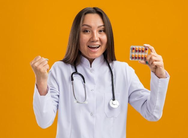 Eccitato giovane dottoressa asiatica che indossa abito medico e stetoscopio che mostra il pacchetto di capsule mediche alla telecamera guardando la parte anteriore facendo un gesto forte isolato sulla parete arancione