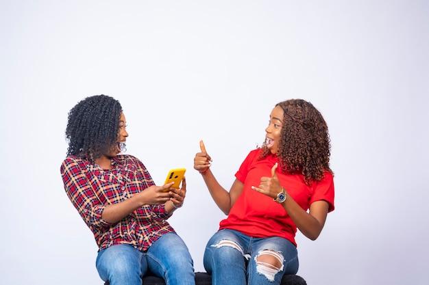 Eccitate giovani donne nere dopo aver visto qualcosa su un telefono, danno il pollice in alto guardandosi l'un l'altro