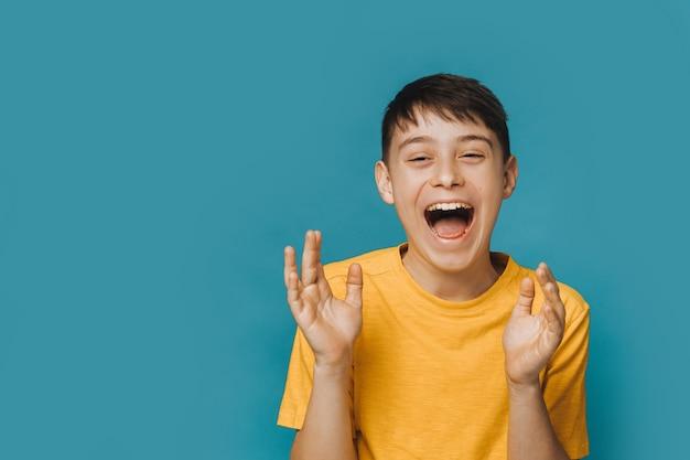 Eccitato ragazzo in maglietta gialla che grida ad alta voce con la bocca spalancata e la faccia felice, batte le mani, grato