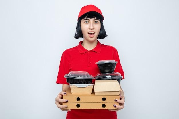 Eccitata giovane donna delle consegne caucasica che tiene in mano contenitori per alimenti e scatole per pizza