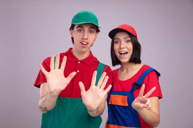 Eccitato giovane coppia in uniforme da operaio edile e berretto che mostra dieci con le mani ragazza che mostra due con la mano
