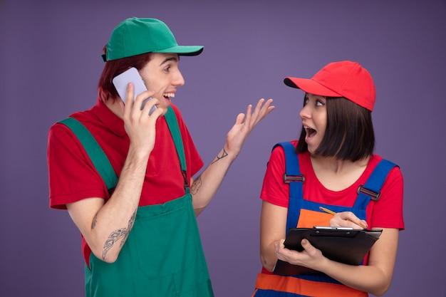 Eccitato giovane coppia in uniforme da operaio edile e berretto guardando l'altro ragazzo parlando al telefono mostrando mano vuota ragazza con matita e appunti isolati sul muro viola