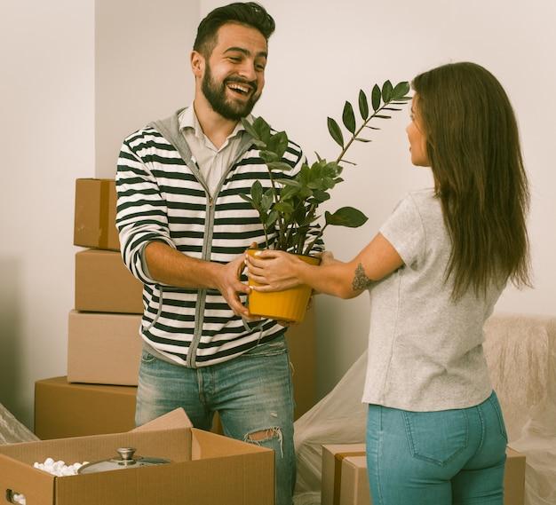 Casa commovente emozionante delle giovani coppie che sta vicino insieme alle piante in loro mani.