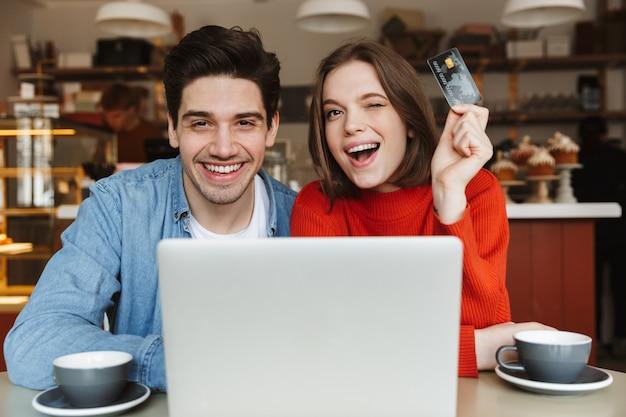 Giovani coppie emozionanti che mostrano la carta di credito