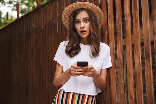 Ragazza emozionante che tiene il telefono cellulare mentre levandosi in piedi alla parete di legno all'aperto