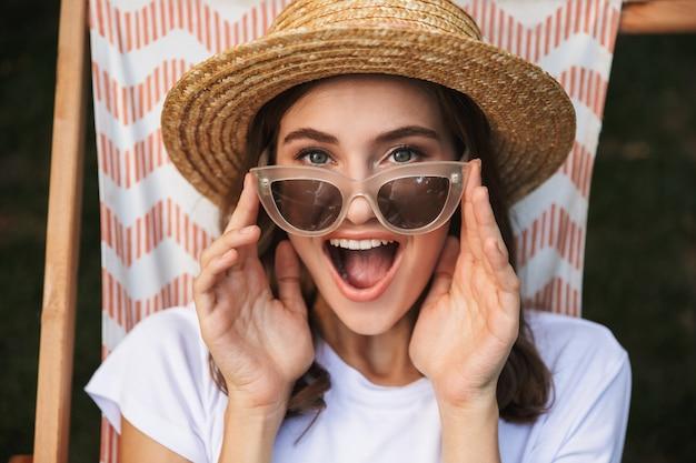 Eccitato giovane ragazza in occhiali da sole che riposa su un'amaca presso il parco cittadino all'aperto in estate