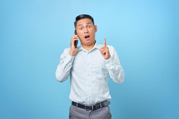 Eccitato giovane uomo d'affari bello parlare al telefono cellulare e puntare il dito con un'idea