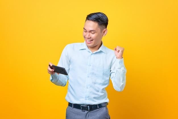 Eccitato giovane uomo d'affari bello che usa lo smartphone e fa un gesto di vittoria su sfondo giallo