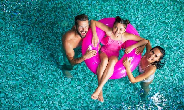 Emozionata e giovane famiglia felice in vacanza nell'hotel termale si rilassa e si diverte in piscina. riposo estivo