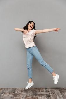 Giovane signora emozionante che salta indicare da parte.