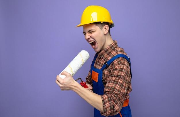 Eccitato giovane costruttore maschio che indossa l'uniforme tenendo la spazzola a rullo di vernice e canta