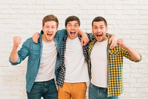 Giovani amici maschii emozionanti che stanno contro il muro bianco che serra il loro pugno