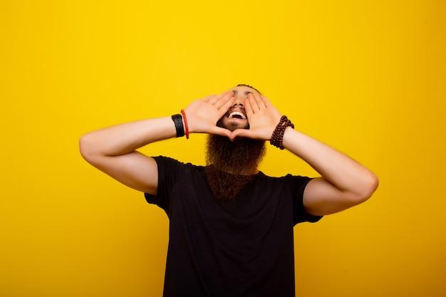 Giovane eccitato che grida con le mani a coppa intorno alla bocca isolata su fondo giallo.