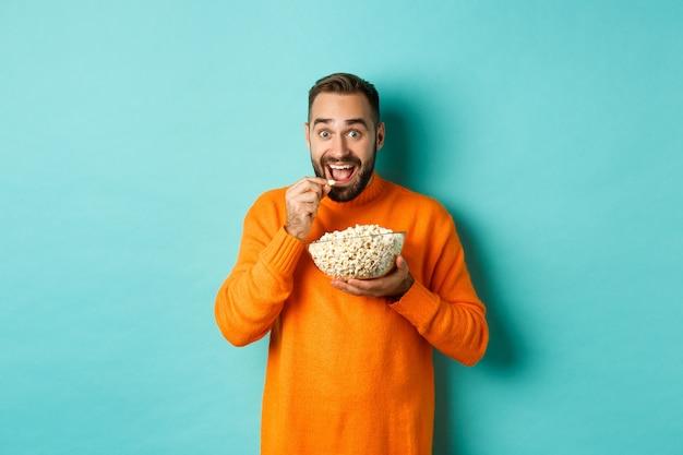 Giovane eccitato che guarda film interessante sullo schermo televisivo, mangia popcorn e sembra stupito, sfondo blu.