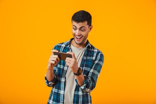 Eccitato giovane uomo che indossa la camicia a quadri in piedi isolato su sfondo arancione, giocando sul cellulare