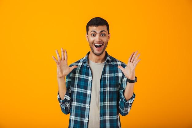 Giovane eccitato che indossa la camicia a quadri in piedi isolato sopra la parete arancione