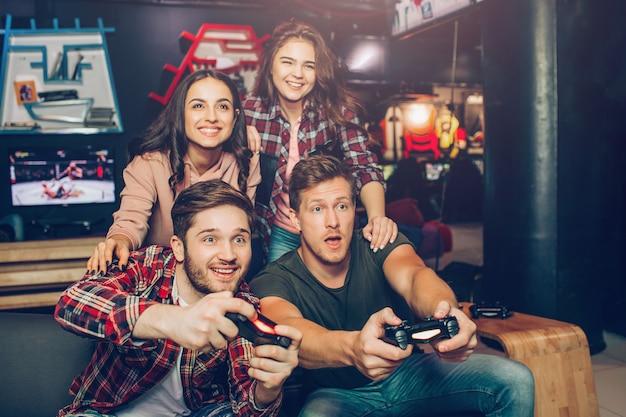 I giovani emozionanti si siedono sul sofà nella stanza di gioco. tengono i joystick e giocano. le giovani donne siedono dietro ed esultano. la gente guarda avanti.