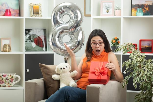 Eccitata giovane bella donna con gli occhiali che si apre e guarda la confezione regalo seduta sulla poltrona in soggiorno a marzo la giornata internazionale della donna