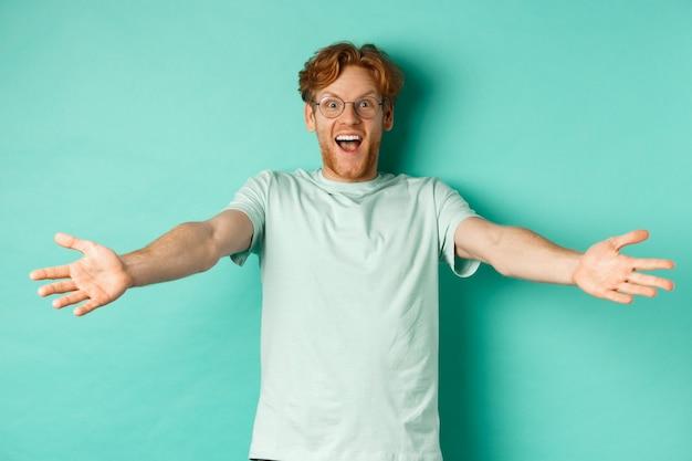 Eccitato giovane ragazzo dai capelli rossi con gli occhiali allunga le mani in un caloroso benvenuto, ti invita e sorridi amichevole alla macchina fotografica, in piedi felice su sfondo turchese