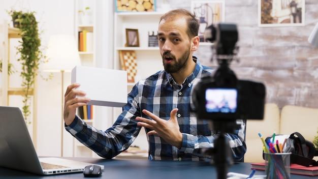 Giovane vlogger emozionante che fa una recensione di un prodotto all'interno della scatola bianca. creatore di contenuti creativi.