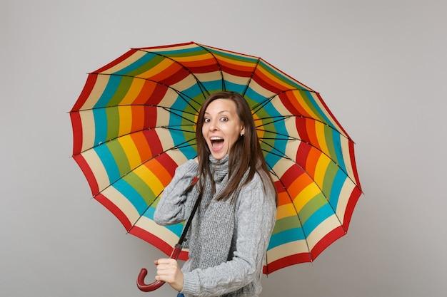 Eccitato giovane donna in maglione grigio, sciarpa tenendo la bocca aperta tenendo ombrello colorato isolato su sfondo grigio. emozioni della gente di stile di vita sano di modo, concetto di stagione fredda. mock up copia spazio.