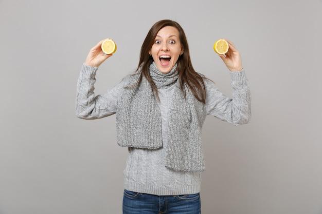 Eccitato giovane donna in maglione grigio, sciarpa tenendo la bocca aperta tenere i limoni isolati su sfondo grigio. stile di vita sano, persone sincere emozioni, concetto di stagione fredda. mock up copia spazio.
