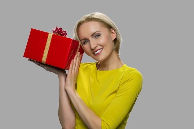 Contenitore di regalo emozionante della tenuta della giovane donna. regalo a sorpresa per il compleanno o la festa della donna. concetto di celebrazione delle vacanze.