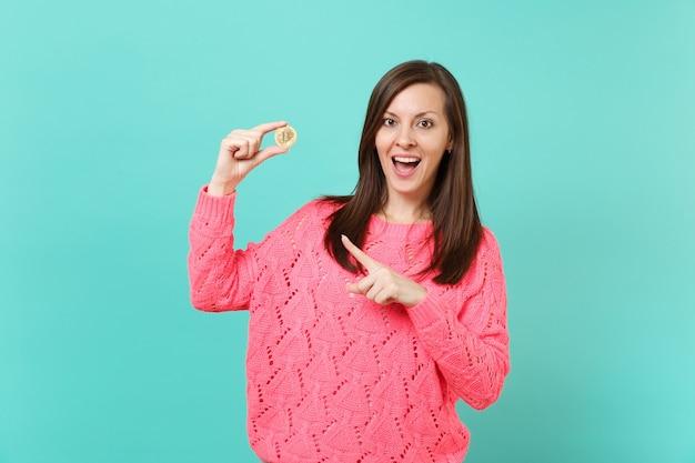 Eccitato giovane donna in maglia maglione rosa puntare il dito indice su bitcoin futura valuta in mano isolato su sfondo blu muro turchese in studio. concetto di stile di vita della gente. mock up copia spazio.