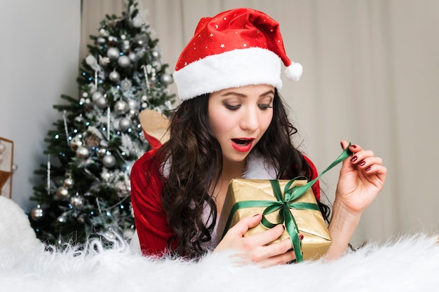 Giovane donna emozionante che apre un regalo di natale. ragazza carina in costume da babbo natale scatena un nastro su un regalo di capodanno sdraiato sul letto sullo sfondo di un albero di natale decorato.