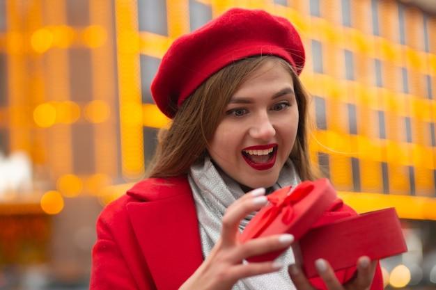 Eccitato giovane donna che apre una confezione regalo di san valentino a forma di cuore su uno sfondo di luci sfocate. spazio vuoto