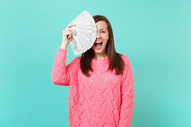 Eccitata giovane donna in maglione rosa che copre l'occhio con un sacco di banconote in dollari, denaro contante, tenendo la bocca spalancata isolata su sfondo blu. concetto di stile di vita della gente. mock up copia spazio.