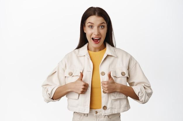 Una giovane donna eccitata valuta un evento fantastico, rimane a bocca aperta, mostra i pollici in su per approvare, concordare o apprezzare, dire di sì, lodare e complimentarsi per una cosa fantastica sul bianco