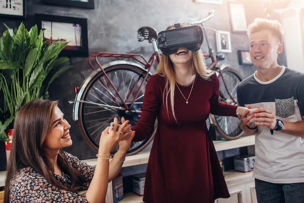 La giovane donna emozionante canta la cuffia avricolare di realtà virtuale con gli amici che tengono le sue mani
