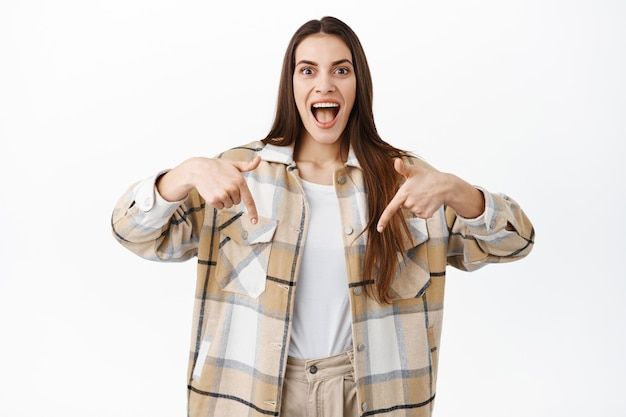 Eccitata giovane donna che sorride e punta verso il basso con una faccia stupita e felice, mostrando un fantastico nuovo affare promozionale, punta al banner del logo con una grande offerta, in piedi sul muro bianco