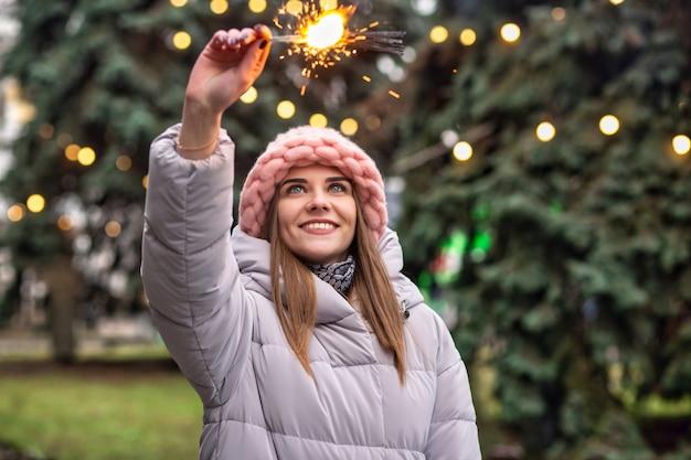 Una giovane donna eccitata indossa un cappello e un cappotto a maglia rosa che si divertono con le stelle filanti per la strada vicino all'albero di natale