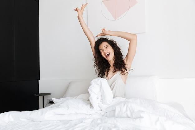 Eccitato giovane donna con i capelli ricci scuri, seduta a letto