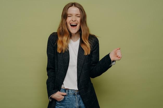 Eccitazione. studio shot di giovane donna sorpresa e felice con capelli castani ondulati in posa in giacca formale scura, top bianco e jeans su sfondo verde con una mano in tasca. traguardi personali