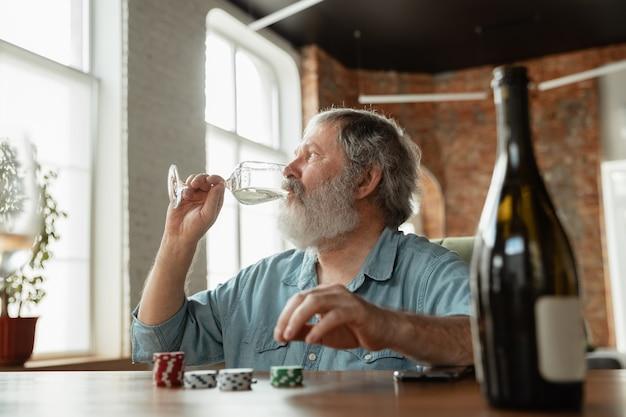 Eccitante. uomo maturo felice che beve vino con gli amici durante il gioco di carte sembra felice, eccitato. uomo caucasico che gioca a casa. emozioni sincere, benessere, concetto di espressione facciale. buona vecchiaia.