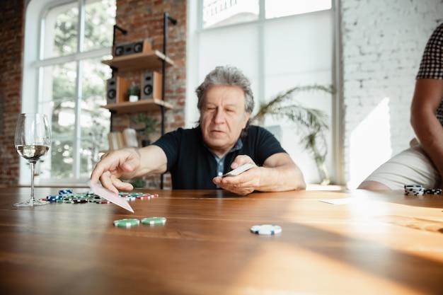 Eccitante. felice uomo maturo giocando a carte e bevendo vino con gli amici. sembra felice, eccitato. uomo caucasico che gioca a casa. emozioni sincere, benessere, concetto di espressione facciale. buona vecchiaia.