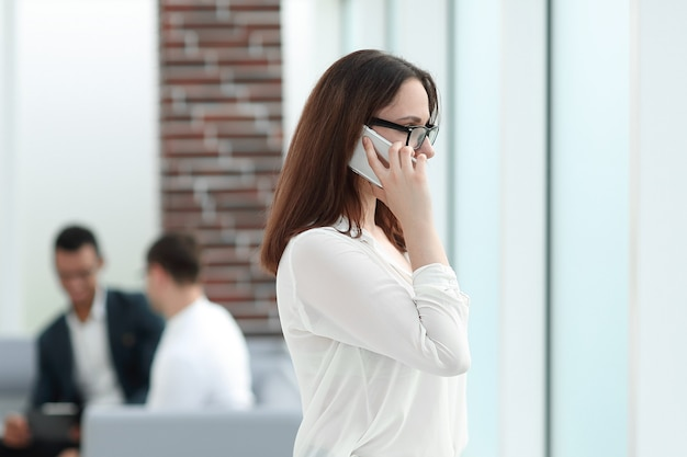 Donna esecutiva di affari che comunica sullo smartphone mentre levandosi in piedi in ufficio
