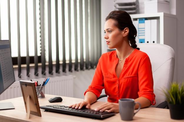 Donna di affari esecutiva nell'ufficio del posto di lavoro che lavora al progetto corporativo di finanza. datore di lavoro concentrato di successo con una carriera impegnata seduto alla scrivania in ufficio utilizzando un pc moderno.