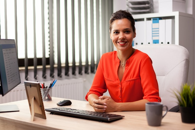 Imprenditore finanziario freelance esecutivo che indossa una camicetta rossa che sorride alla macchina fotografica sul posto di lavoro. donna sicura di successo nel marketing seduto alla scrivania sul posto di lavoro utilizzando il computer.