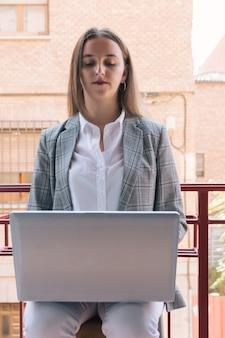 Ragazza esecutiva che lavora con il suo laptop dal suo balcone. lavoro di concetto da casa. pandemia di coronavirus.