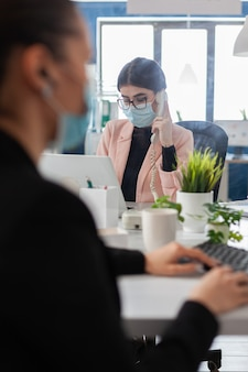 Direttore esecutivo che parla al telefono fisso spiegando la strategia di marketing al collega che lavora al rapporto dell'azienda nell'ufficio di avvio. donna d'affari con maschera medica contro covid19 durante la pandemia globale